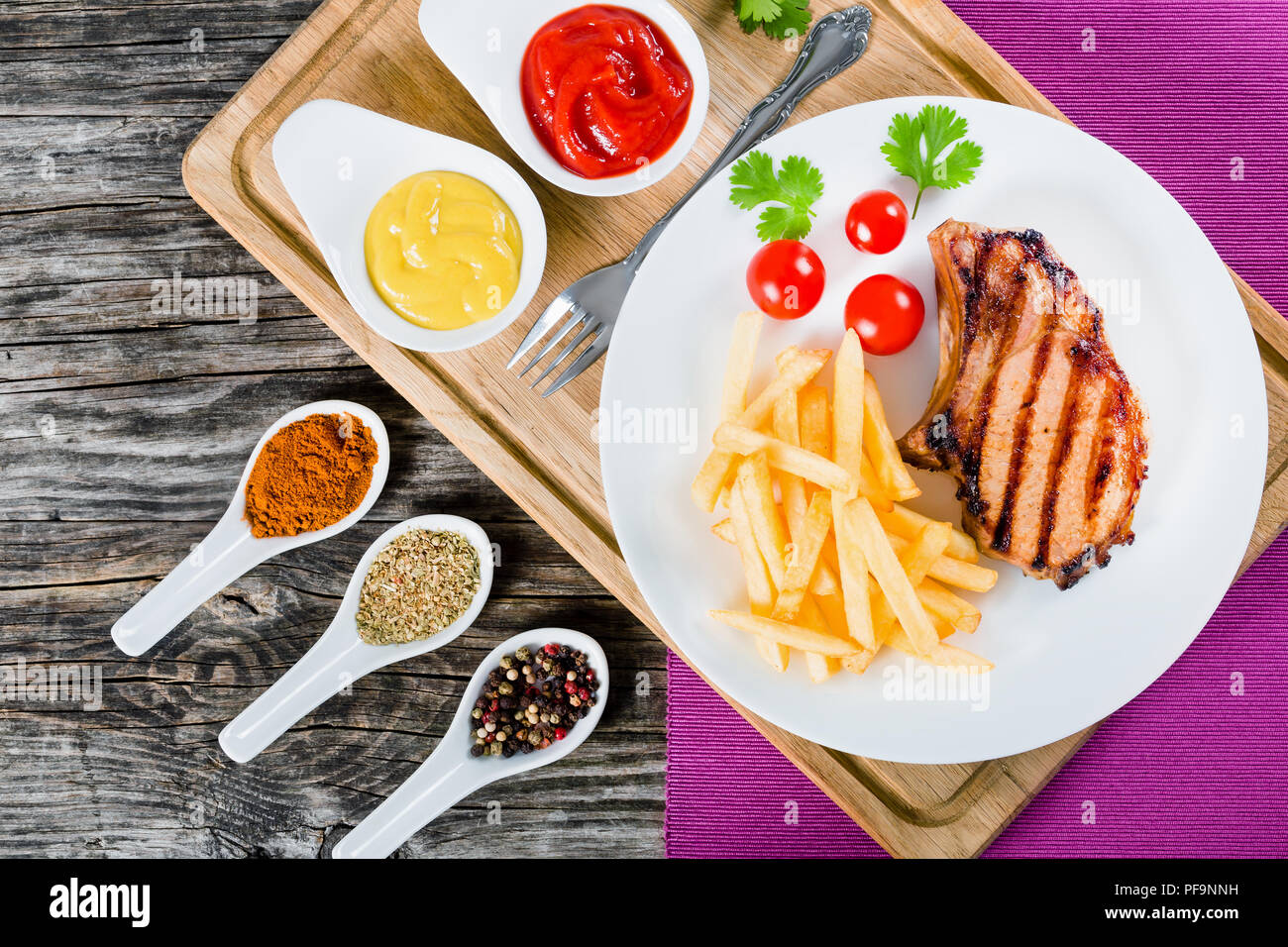 grilled pork chops on a white dish with french fries, cherry ...