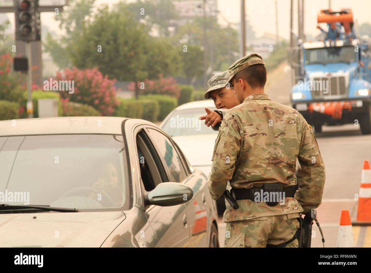 US Army Spcs Rodavlas Manliclic and Mailo Gonzalez of the 870th Military Police Company, 185th Military Police Battalion, 49th Military Police Brigade, California Army National Guard, control a traffic point at an active intersection July 29 in Redding, California, where the Carr Fire passed through and continued to expand, July 29, 2018. Image courtesy Staff Sgt. Edward Siguenza/California National Guard. () - Stock Image