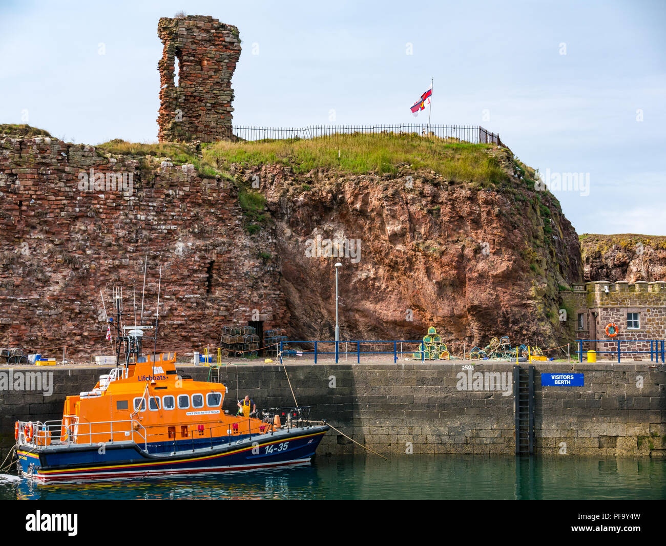 RNLI Lifeboat moored in harbour, with ruined Dunbar Castle, Dunbar, East Lothian, Scotland, UK - Stock Image