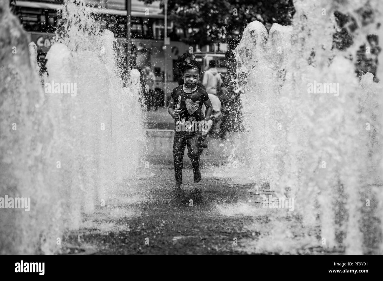 Girl plays in water fountains in Piccadilly Gardens in Manchester City Centre, UK - Stock Image