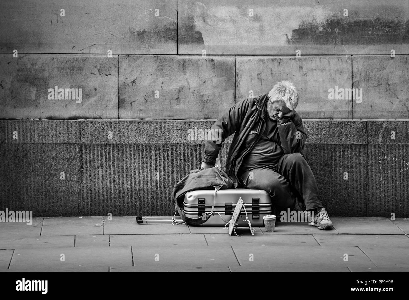 Homeless Man with suitcase asleep on the streets of Manchester City Centre, UK - Stock Image
