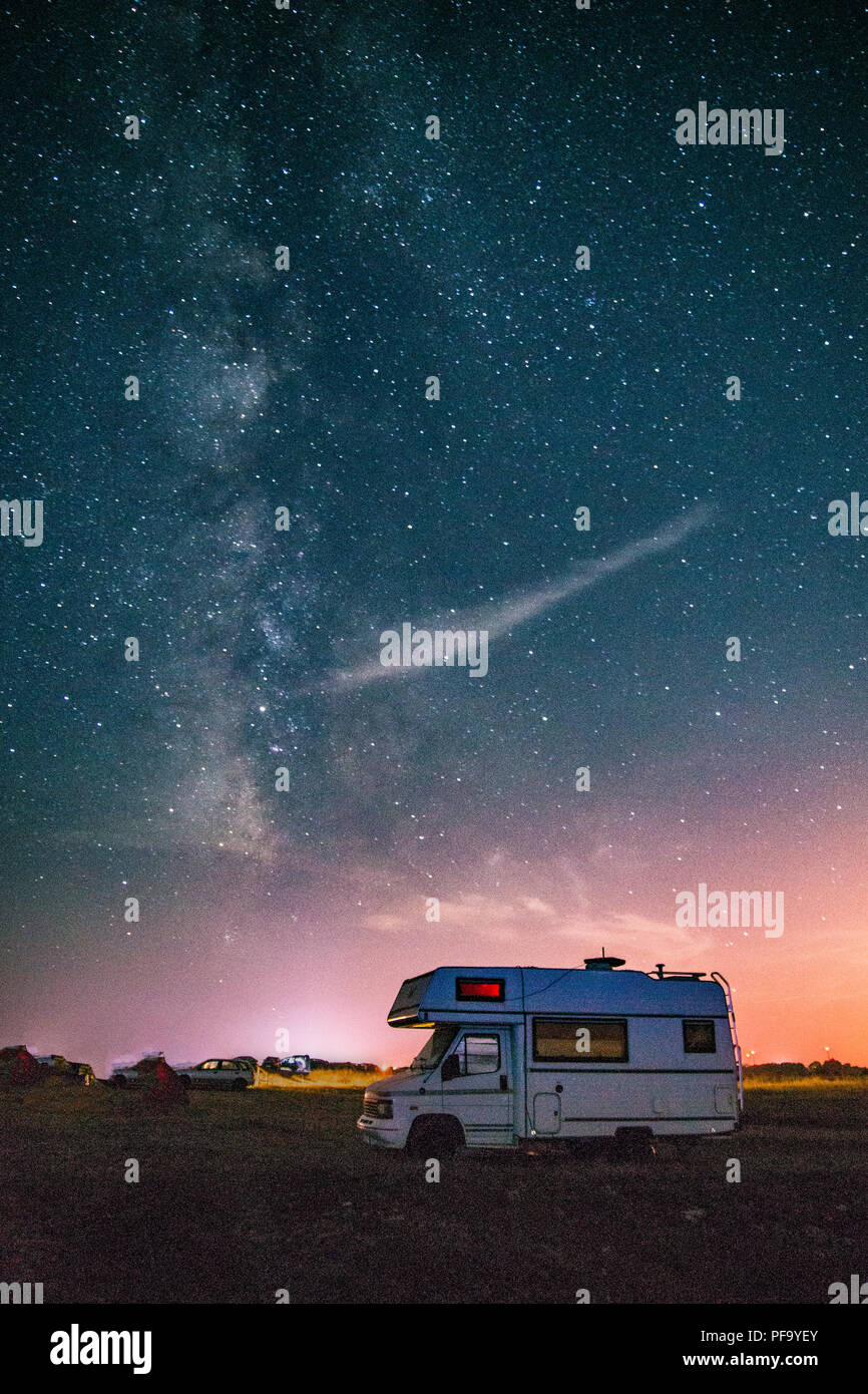 Camper van camping with the Milky way in the background - Stock Image