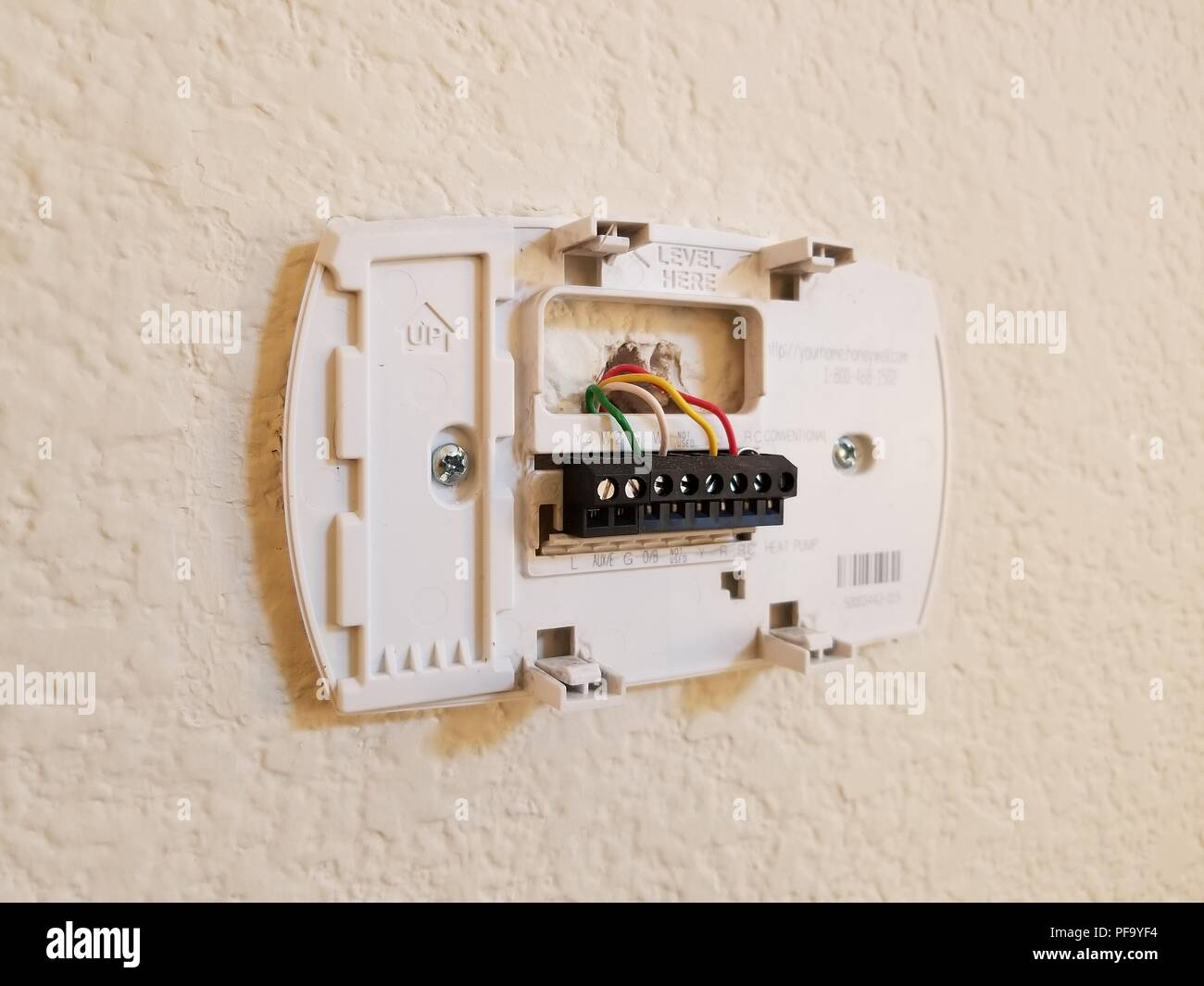 Installation of a programmable thermostat, showing low-voltage wires  inserted into thermostat back plate, in a suburban home, San Ramon,  California, May 4, ...