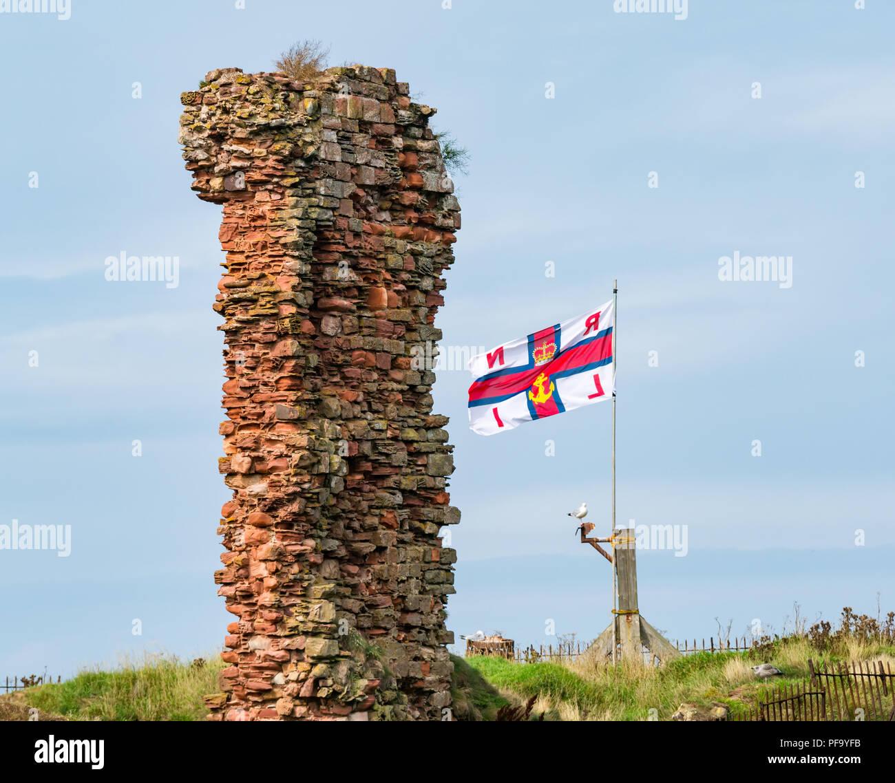 Ruined wall of Dunbar Castle with RNLI flag flying, Dunbar harbour, Dunbar, East Lothian, Scotland, UK - Stock Image