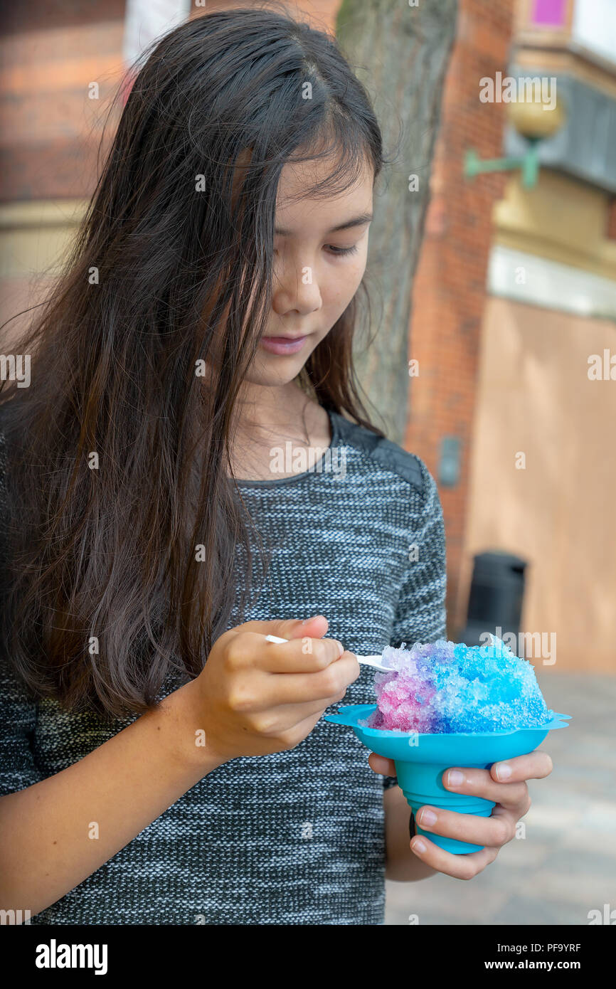 English/Thai teenage girl with long black hair eats a blue Slush in Warrington Town Centre - Stock Image