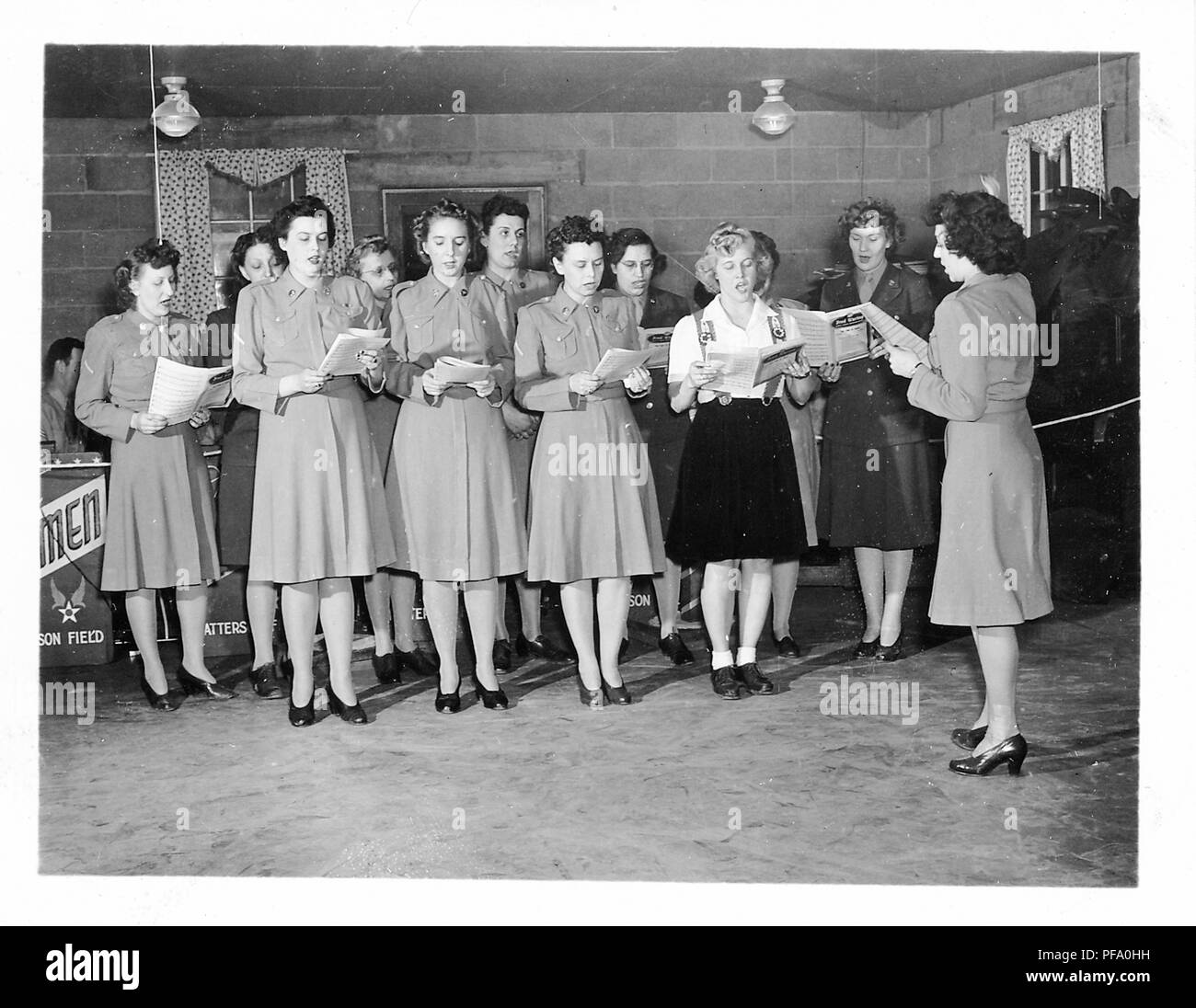 Black and white photograph, showing a group of women, most wearing military skirts and jackets, one in civilian skirt and top, standing indoors, and singing from musical scores that they hold in their hands, likely photographed in Ohio during World War II, 1945. () - Stock Image