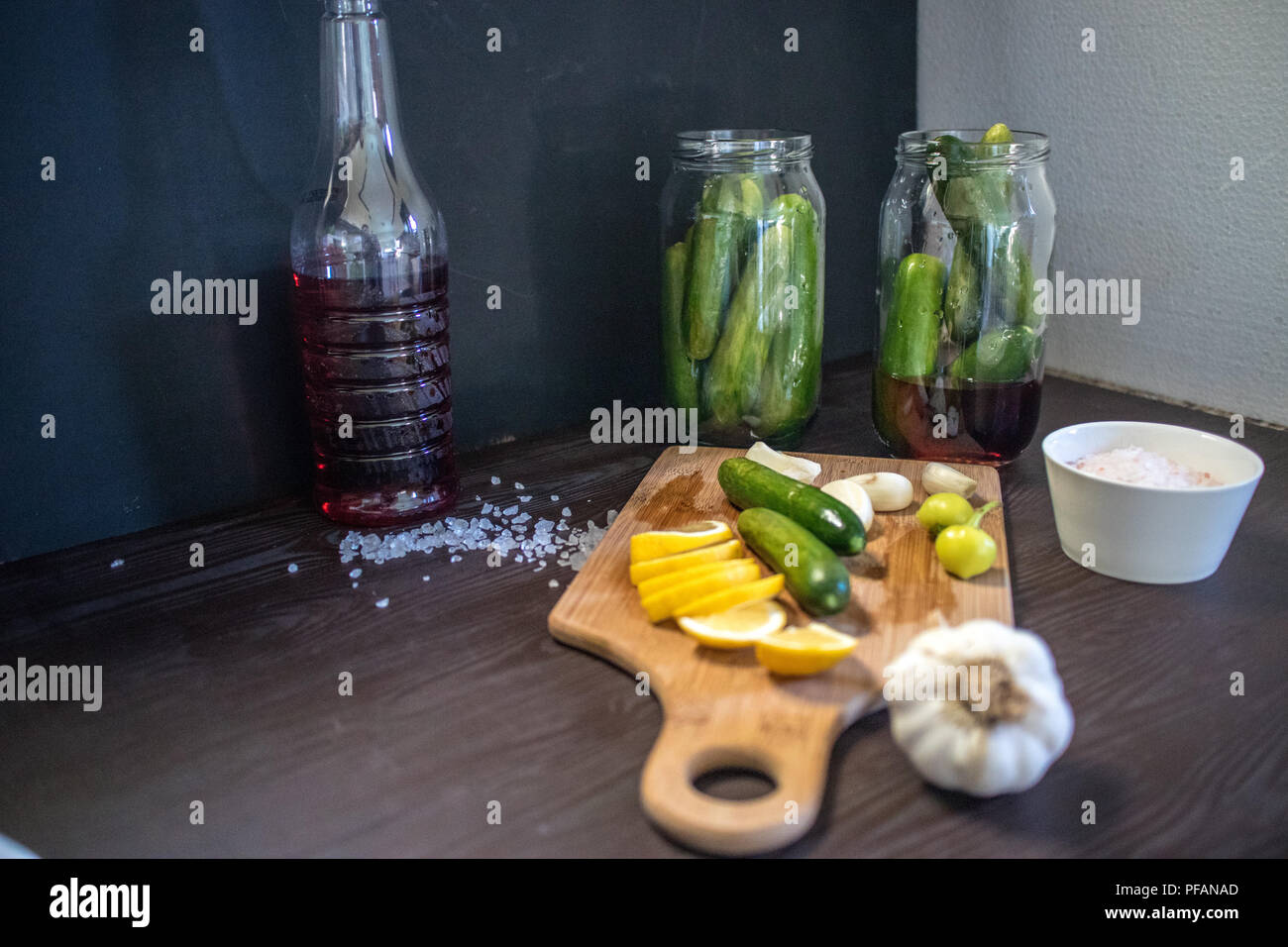 pickled cucumbers and ingredients, cucumber, garlic, vinegar, lemon, one or two peppers, parsley and coarse rock salt - Stock Image