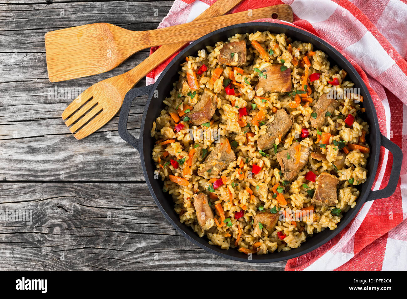 Homemade prepared paella with meat, pepper, vegetables and spices in iron pan with kitchen towel on wooden table, copy space left,  view from above - Stock Image