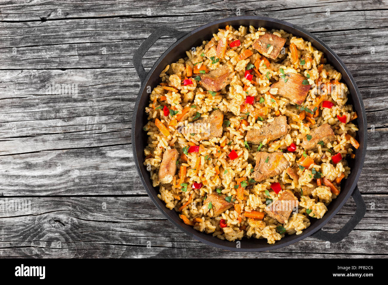 Homemade prepared paella with meat, pepper, vegetables and spices in iron pan on wooden planks, copy space left,  view from above - Stock Image