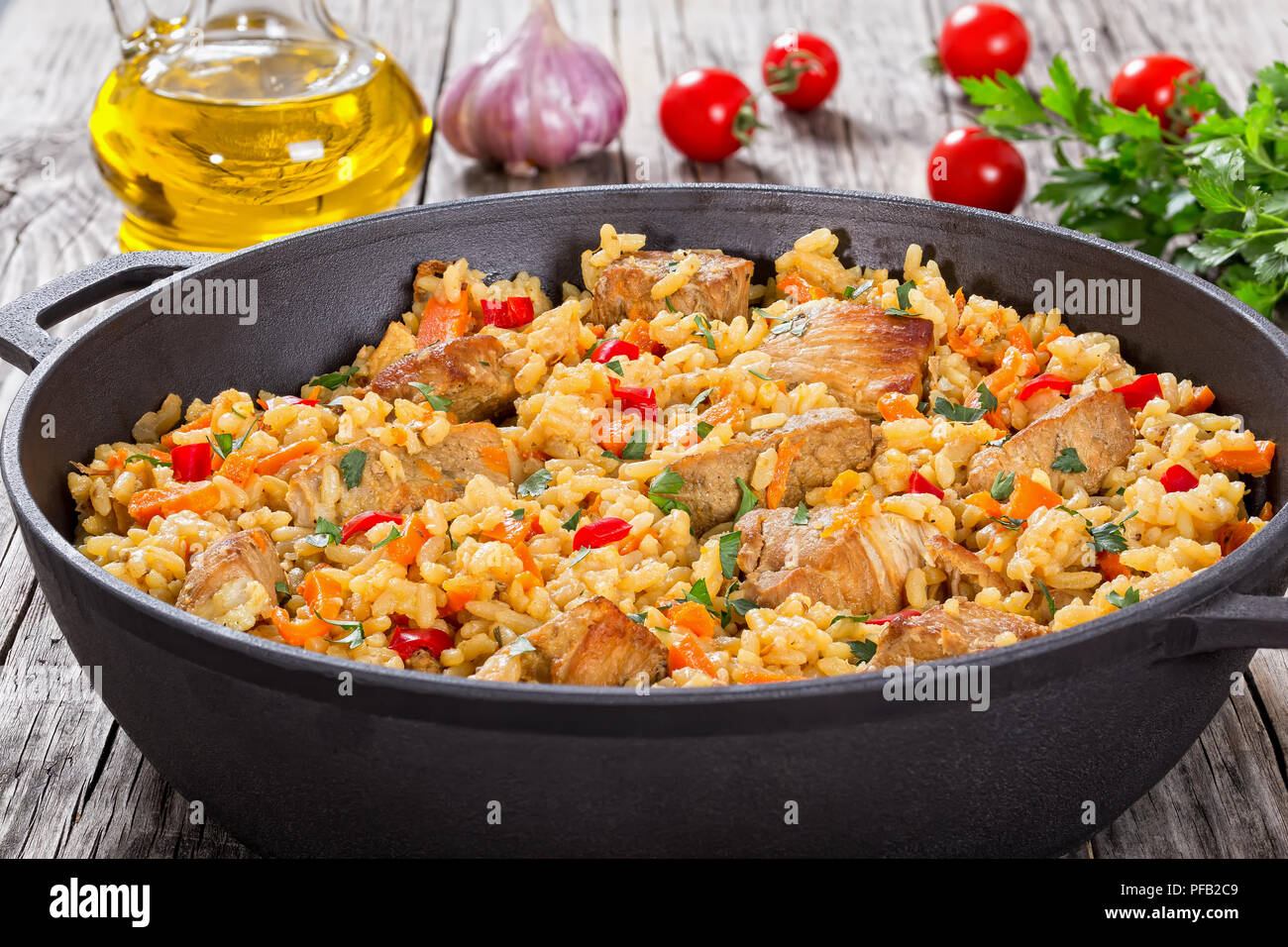 Homemade prepared paella with meat, pepper, vegetables and spices in iron stewpan on wooden planks,  bottle of olive oil,tomatoes,  parsley, garlic on - Stock Image