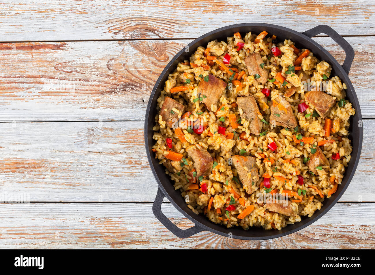 Homemade prepared paella with meat, pepper, vegetables and spices in iron pan on white peeling paint wooden planks, view from above - Stock Image