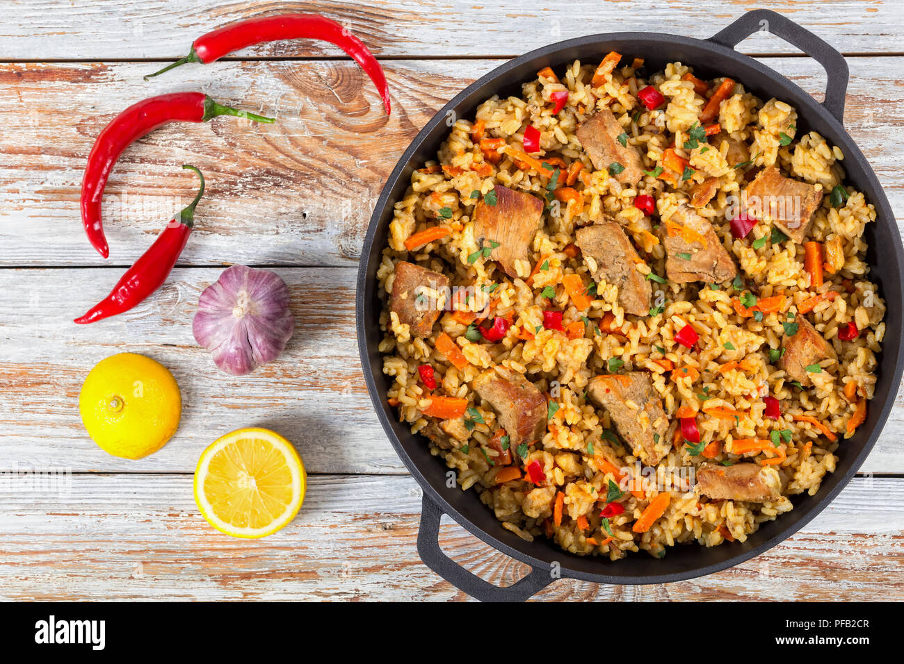 Homemade prepared paella with meat, pepper, vegetables and spices in iron pan on white peeling paint wooden planks, chili pepper , lemon slices and ga - Stock Image