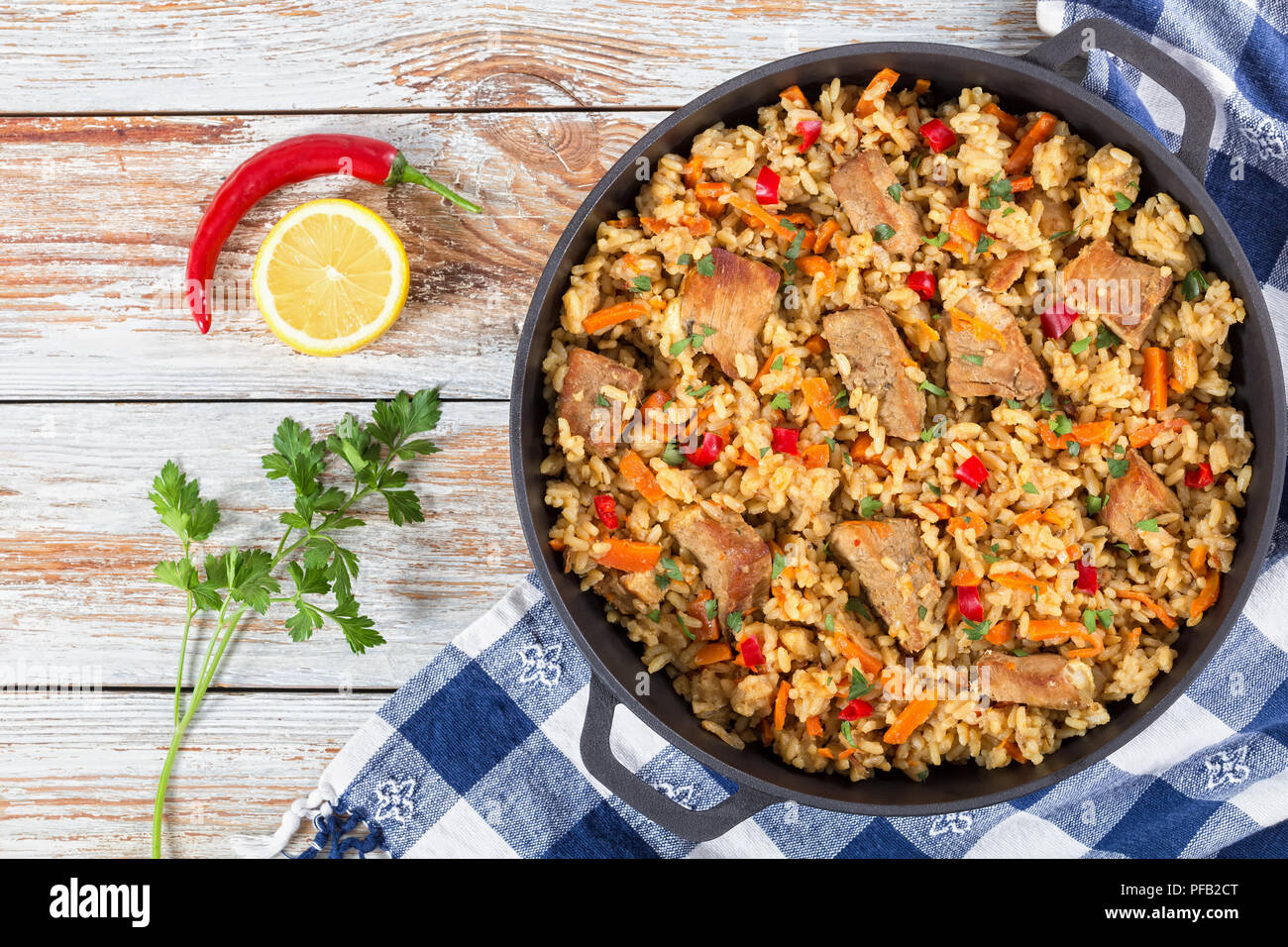 Homemade prepared paella with meat, pepper, vegetables and spices in iron pan on white peeling paint wooden planks, chili pepper , lemon slice and par - Stock Image