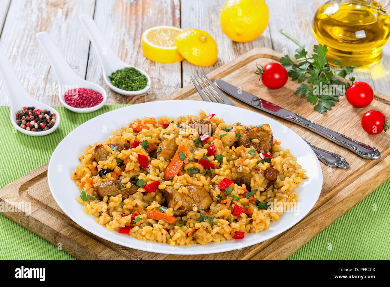tasty paella with meat, pepper, vegetables and spices on platter on cutting board, lemon slice, spices and cherry tomatoes on background, view from ab - Stock Image