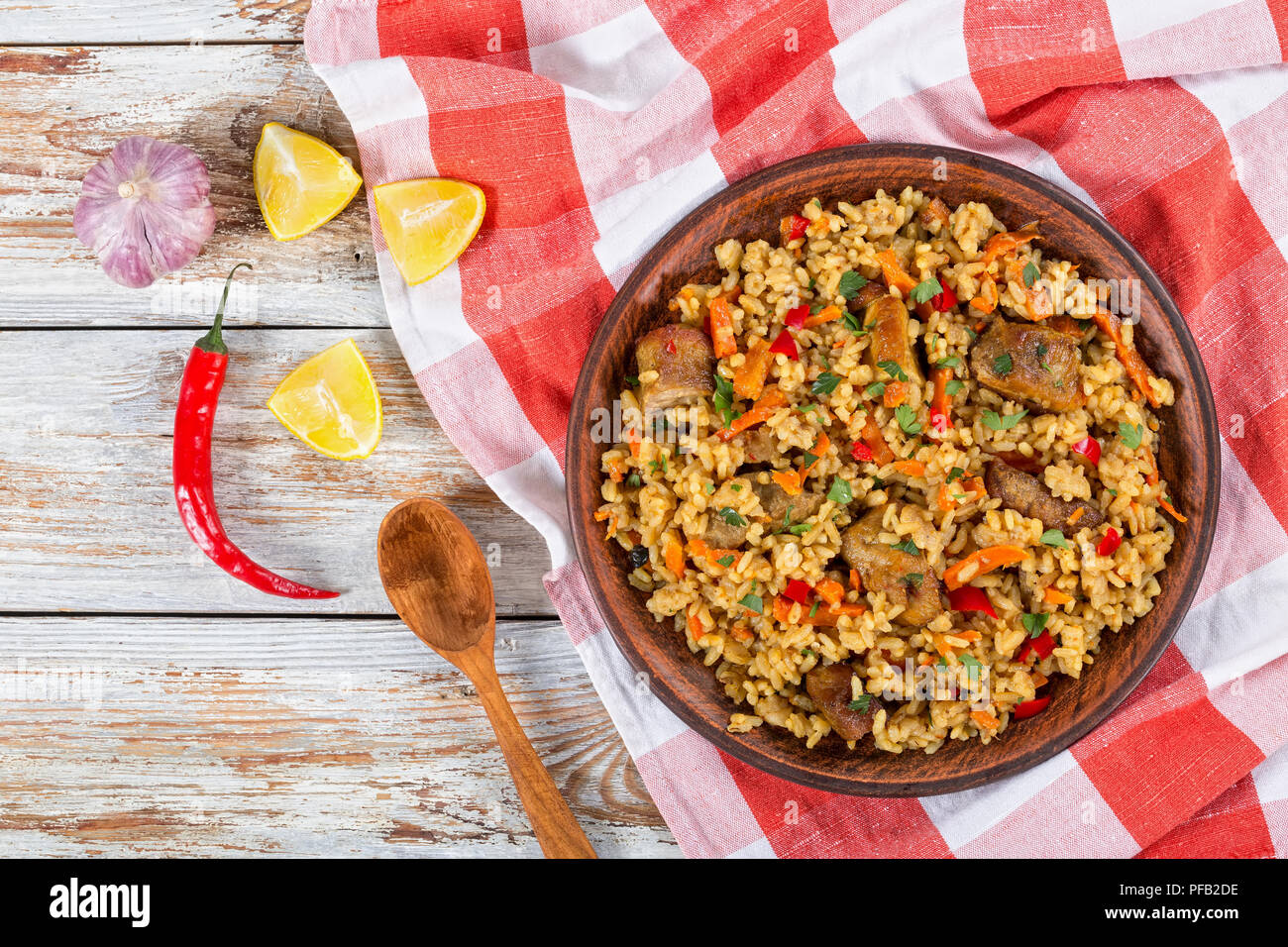 rice with meat, pepper, vegetables and spices on dish, lemon slice, garlic, chili pepper and wooden spoon on white peeling paint planks, view from abo Stock Photo