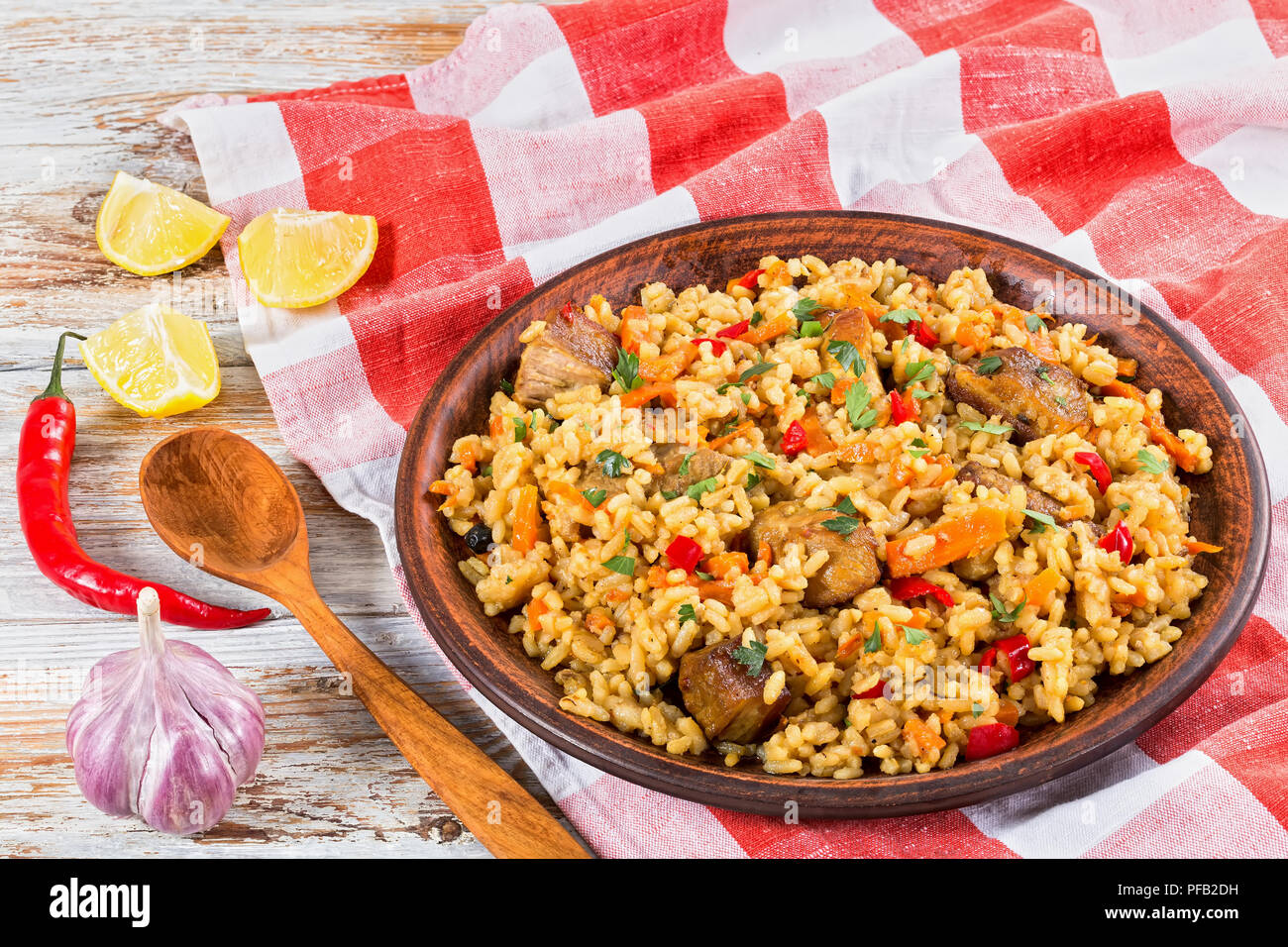 rice with meat, pepper, vegetables and spices on clay dish, kitchen towel,lemon slice, garlic, chili pepper and wooden spoon on white peeling paint pl Stock Photo