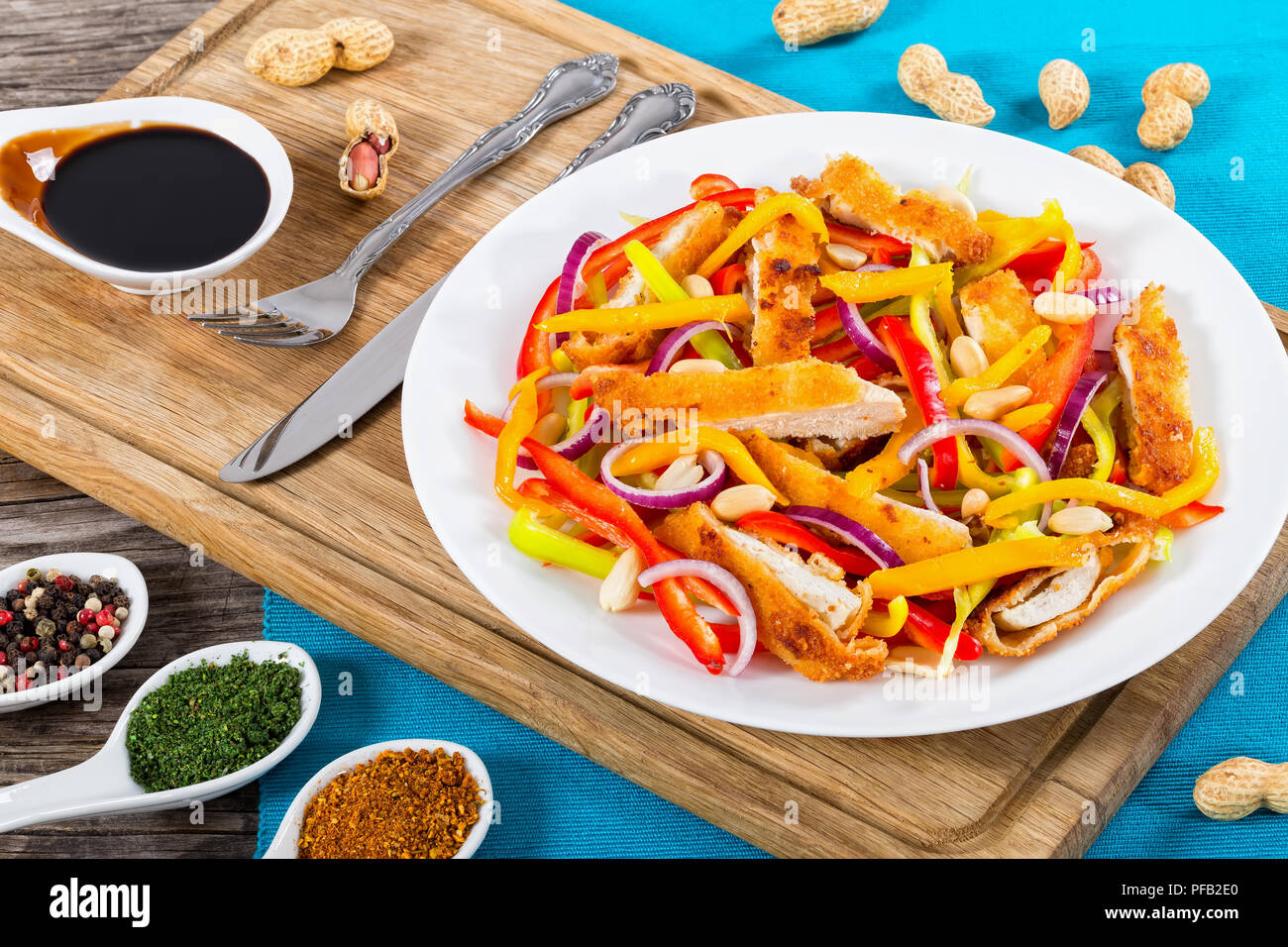 bread crumbed chicken meat, mango, peanuts, bell pepper, red onion salad on white dish with half of  mango cutting in cubes, balsamic vinegar dressing Stock Photo