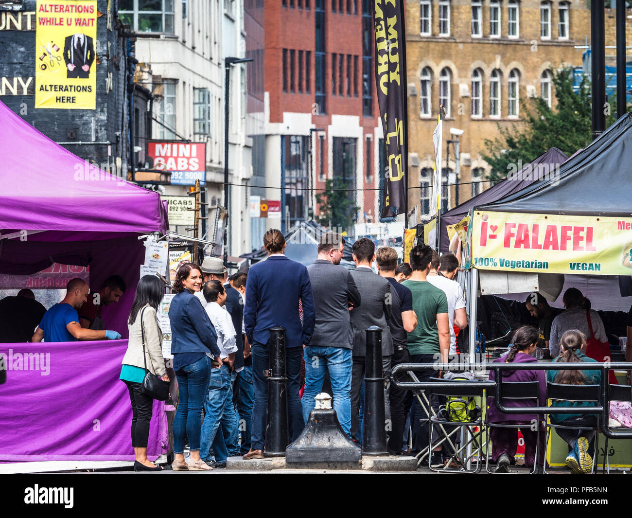 London Street Food Market Petticoat Lane - City workers buy lunch at the food stalls on Petticoat Lane Street Market in East London - Stock Image