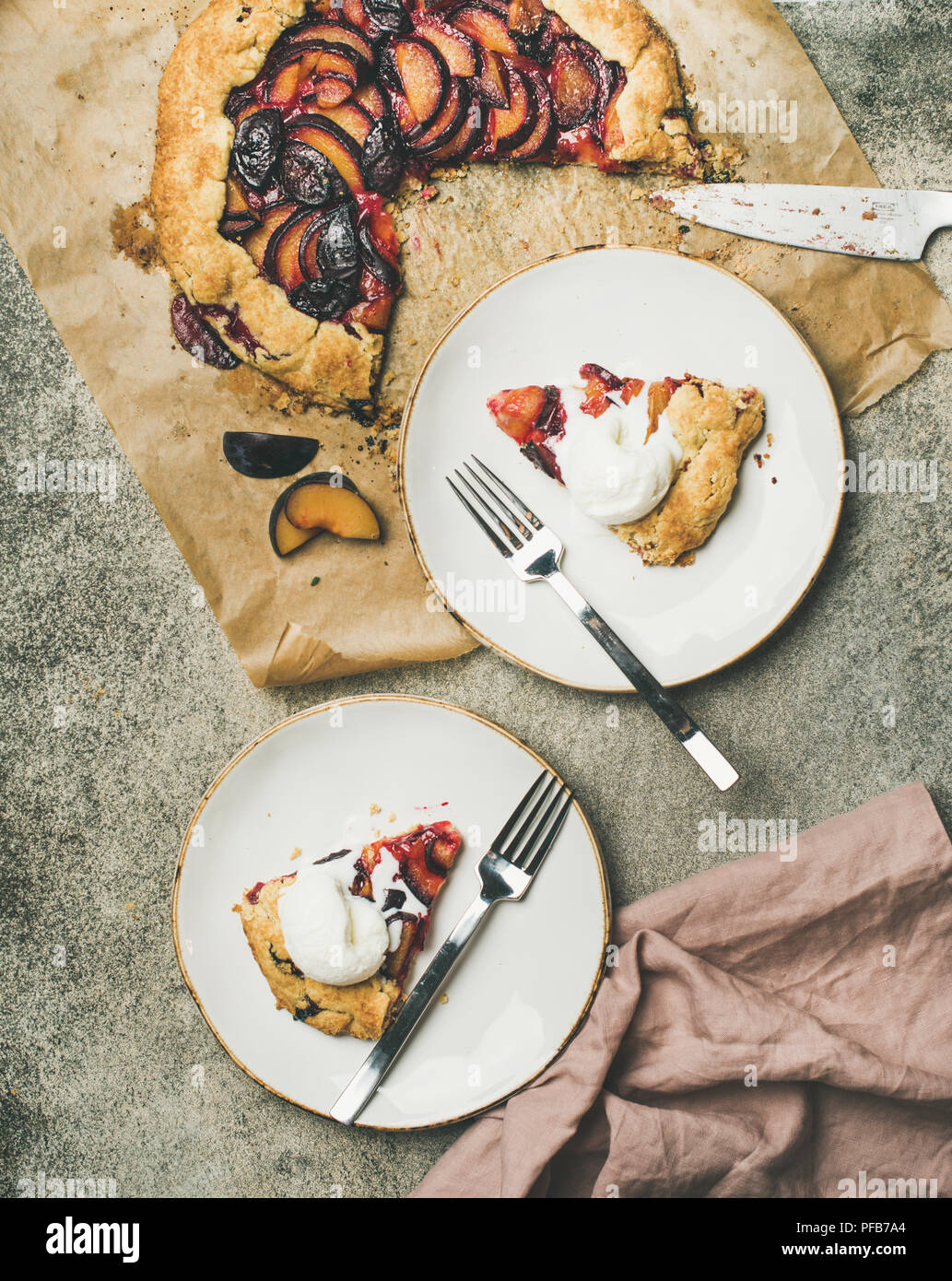 Flat-lay of plum galetta sweet cake pieces in white plates - Stock Image