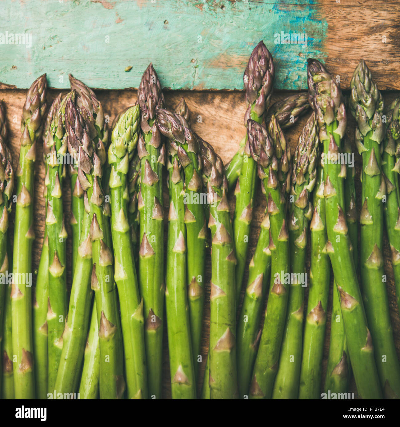 Raw uncooked green asparagus over rustic wooden tray background, square crop - Stock Image
