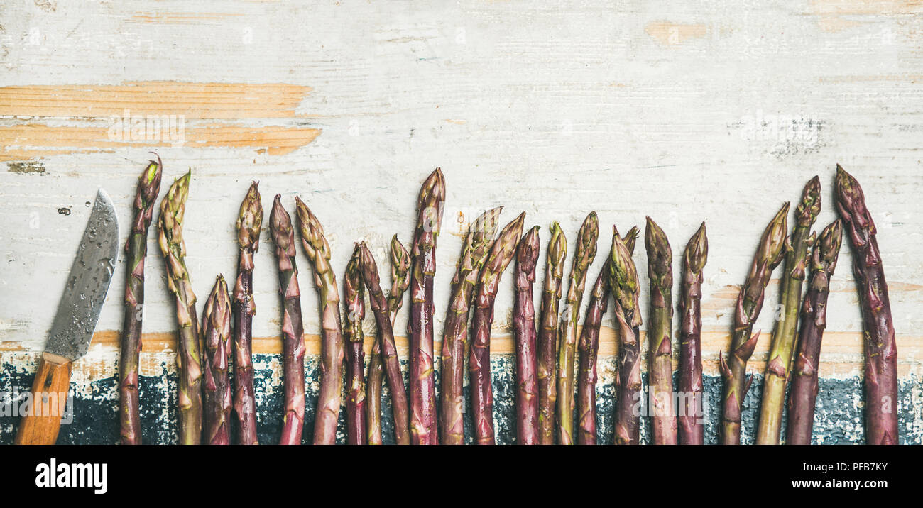 Fresh Raw purple asparagus over rustic wooden background, copy space - Stock Image