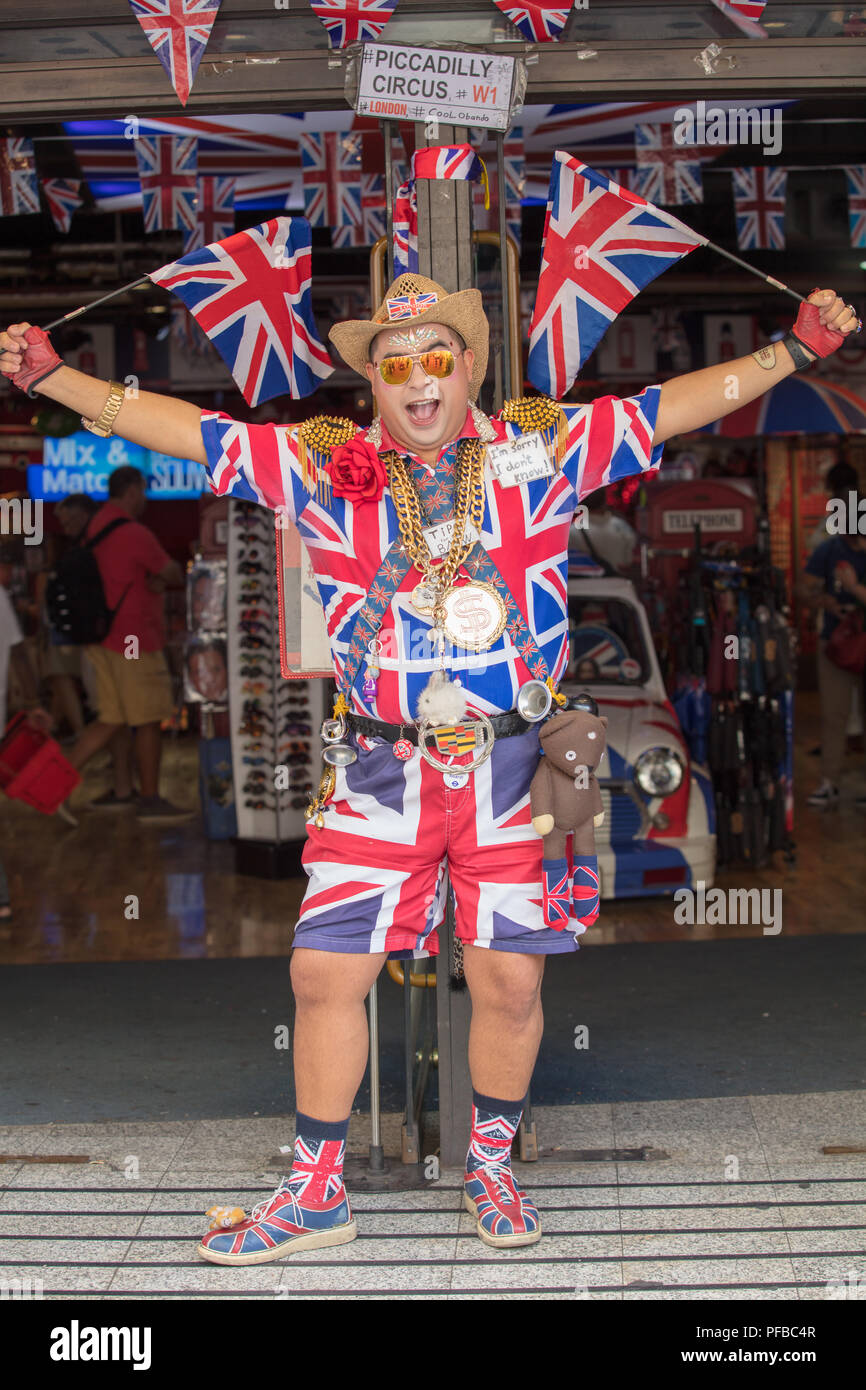 Union Jack dressed entertainer, waving flags, entertaining tourists, at entrance door of souvenir shop, Piccadilly Circus, London, UK. - Stock Image
