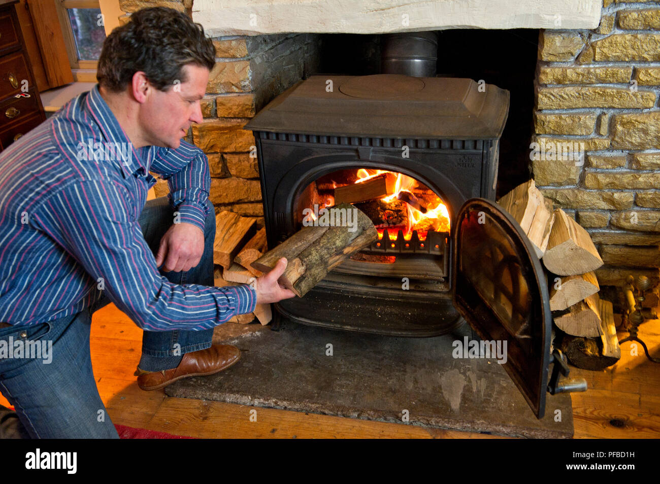 A man feeding logs into a wood burning stove - Stock Image