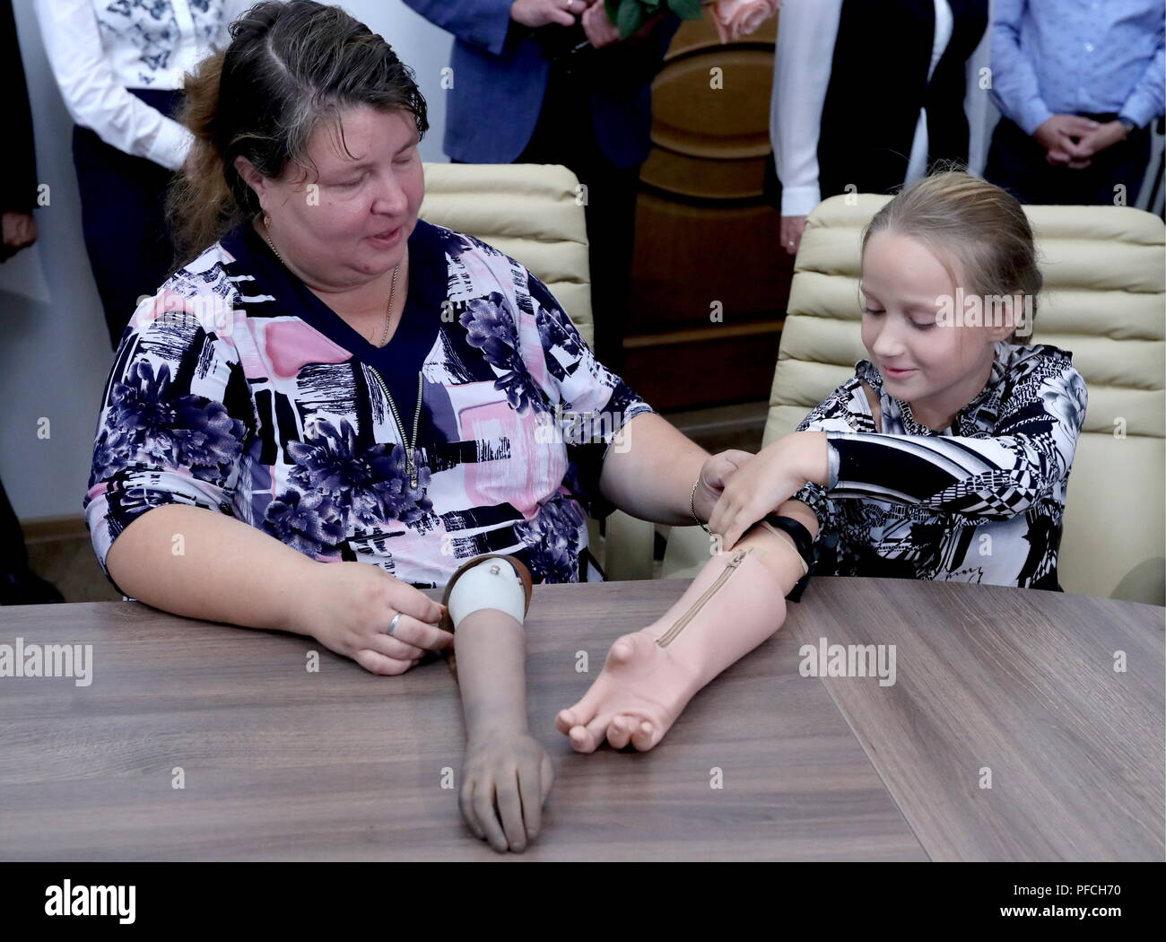 Veliky Novgorod, Russia. 21st Aug, 2018. VELIKY NOVGOROD, RUSSIA - AUGUST 21, 2018: Born with a congenital hand malformation, Maria Gaidukova (R), 9, with mother receive a modular bionic prosthetic hand after two weeks of tests; developed by Veliky Novgorod's Tekhbionik scientific research company led by engineer Stanislav Muravyov (not pictured), and unparalleled in Russia, the prosthesis features three different grip patterns controlled by electrical impulses in an operator's muscles. Alexander Demianchuk/TASS Credit: ITAR-TASS News Agency/Alamy Live News Stock Photo