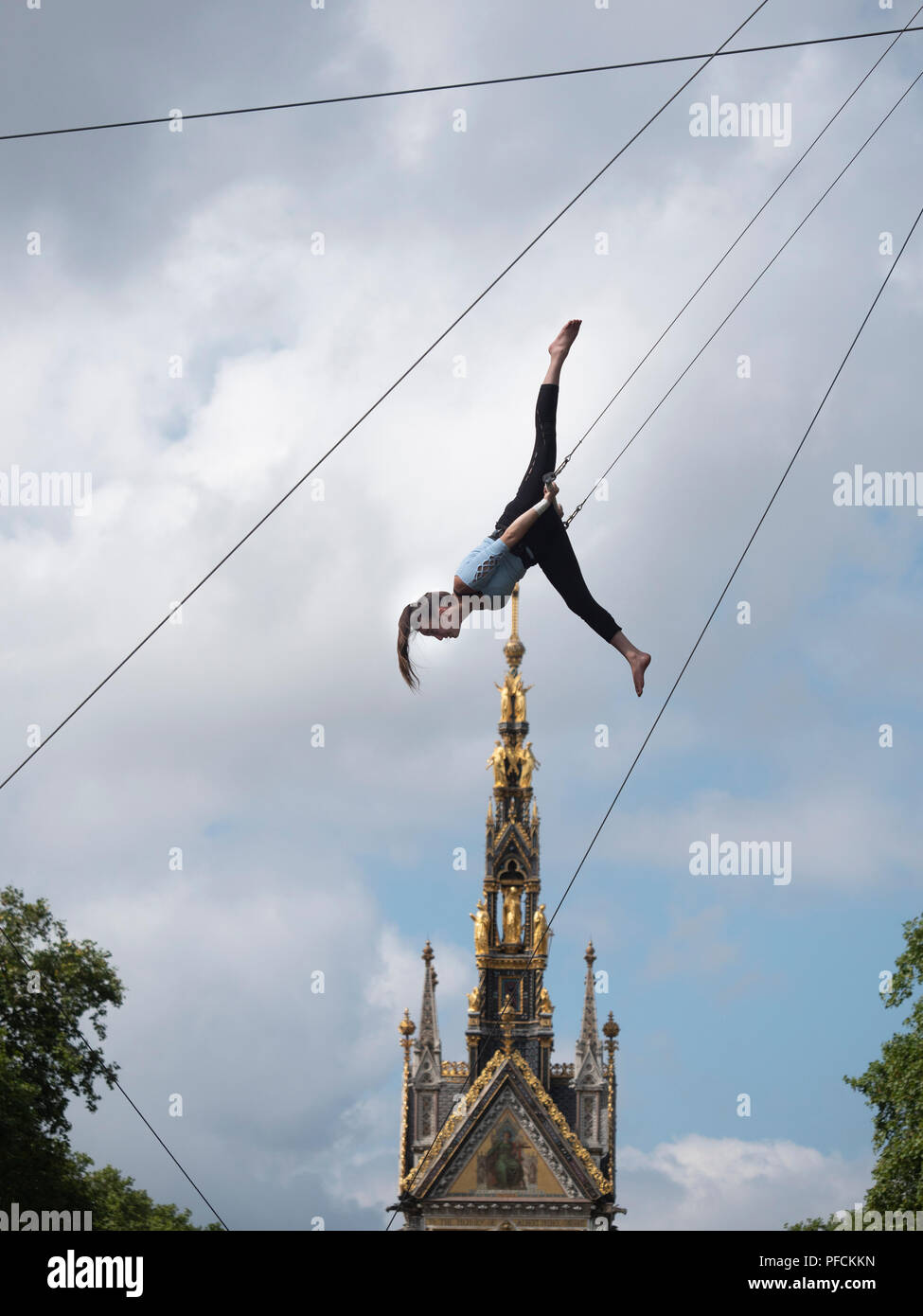 London, UK. 21st August, 2018. Young women keep cool in 27c heat by appearing to fly over the Albert Memorial in Kensington, London. They are they training with the Flying Trapeze School (www.gorillacircus.com) Credit: David Thorpe/Alamy Live News - Stock Image