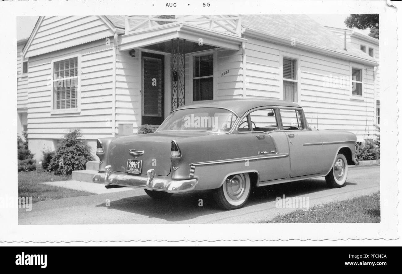 Black and white photograph, showing a two-tone, hard-top, Chevrolet Bel Air parked in a driveway in front of a small, light-colored house, with siding and a covered front porch, likely photographed in Ohio, August, 1955. () - Stock Image