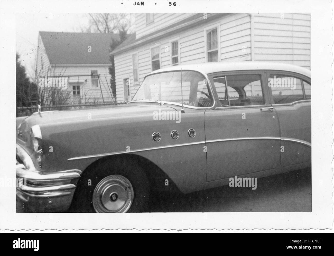 Black and white photograph, showing a close-up, partial profile view of a two-tone, hardtop Chevrolet Bel Air, parked in a driveway, with part of a small house visible in the background, likely photographed in Ohio, 1956. () - Stock Image