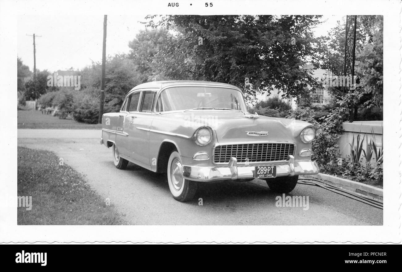 Black and white photograph, showing a two-tone, hard-top Chevrolet Bel Air, with an Ohio license plate, parked in a driveway, with grass, trees, and part of a house visible in the background, August, 1955. () - Stock Image