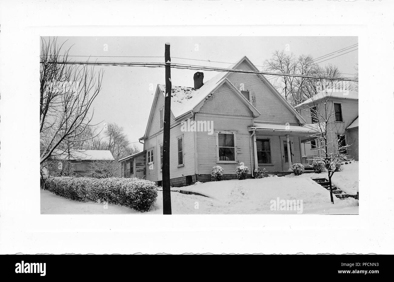 Black and white photograph, showing a small, light-colored house, with siding, a covered front porch, and snow visible on the roof, front yard, hedges, leafless trees, and electrical posts, likely photographed in Ohio in the decade following World War II, 1950. () - Stock Image