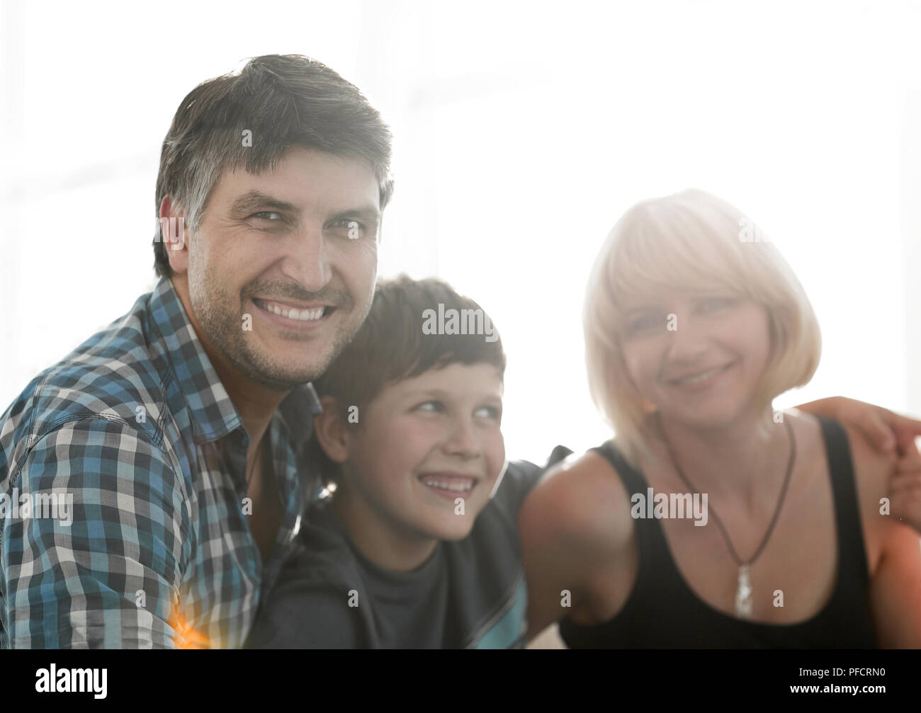 Parents and their son sit huddled in the living room and smiling Stock Photo