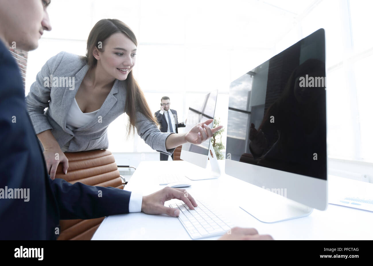 business woman pointing at the computer screen. - Stock Image