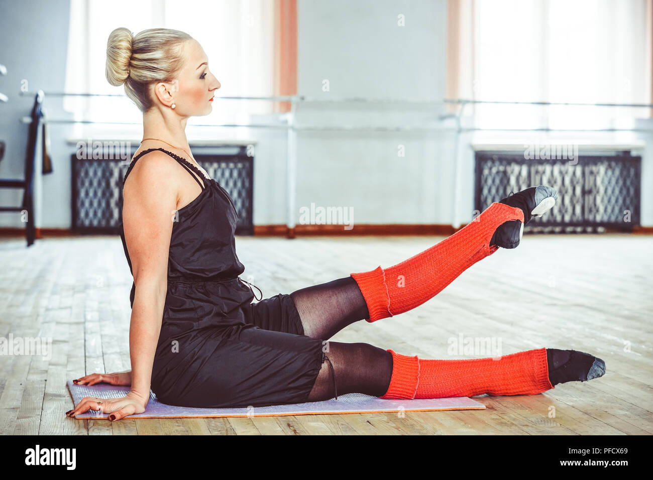 the dancer makes the warm-up in the ballet hall - Stock Image