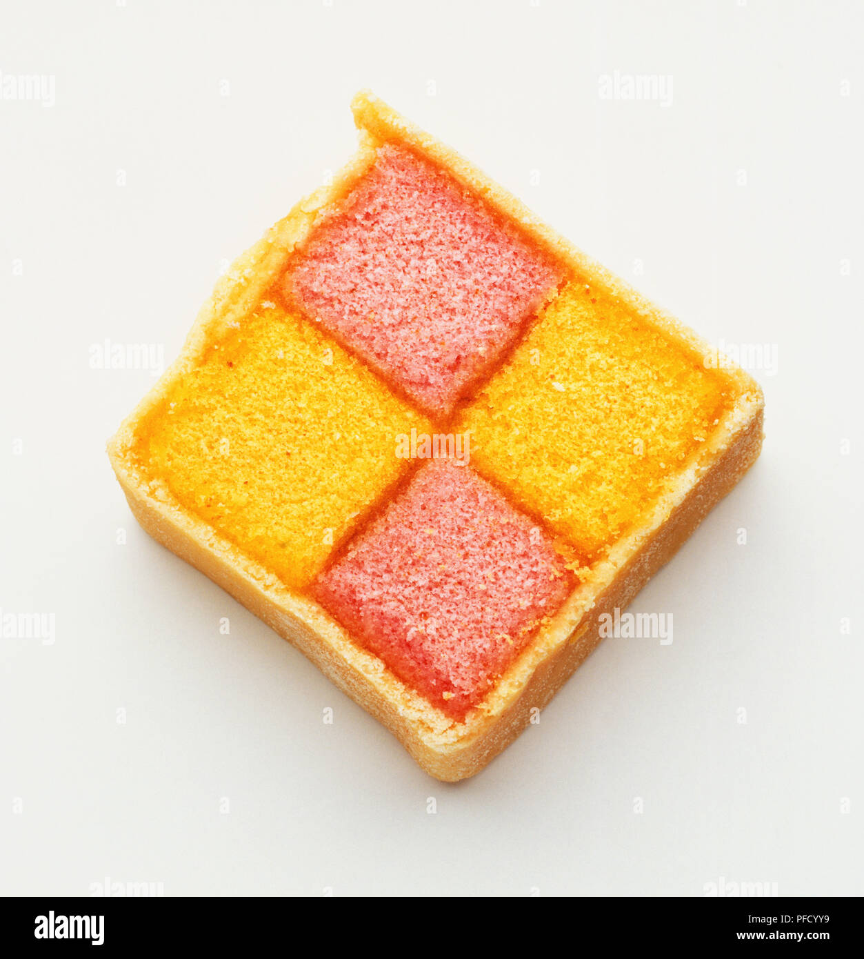 Square slice of iced pink and yellow sponge Battenburg cake, close up. - Stock Image