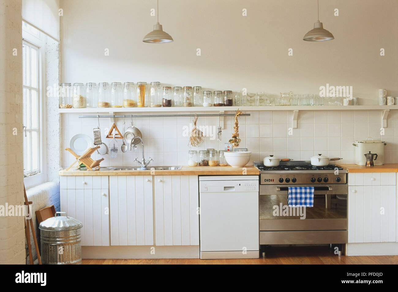Kitchen with white wooden cupboards, pendant lights, long shelf