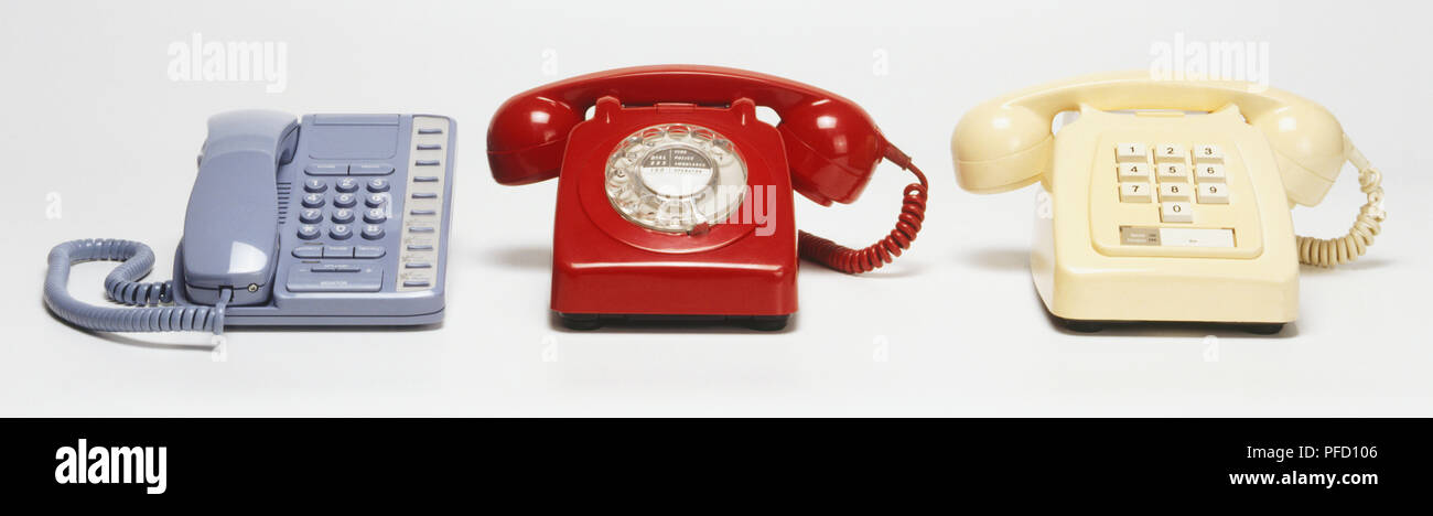 Three desk phones, two with chunky bases, rotary dial, respectively buttons for dialling, receivers across top, one with flat base, receiver on left, buttons for dialling - Stock Image