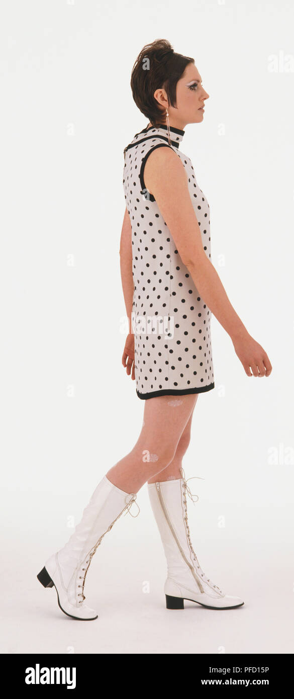 Woman wearing a white miniskirt with black spots and white boots - Stock Image