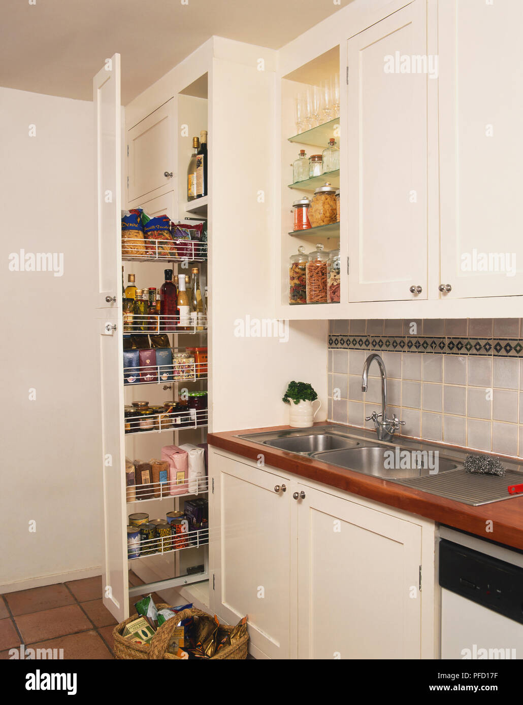 Pull-out kitchen unit stacked with condiments, tins and dry ingredients, next to double sink, side view. - Stock Image