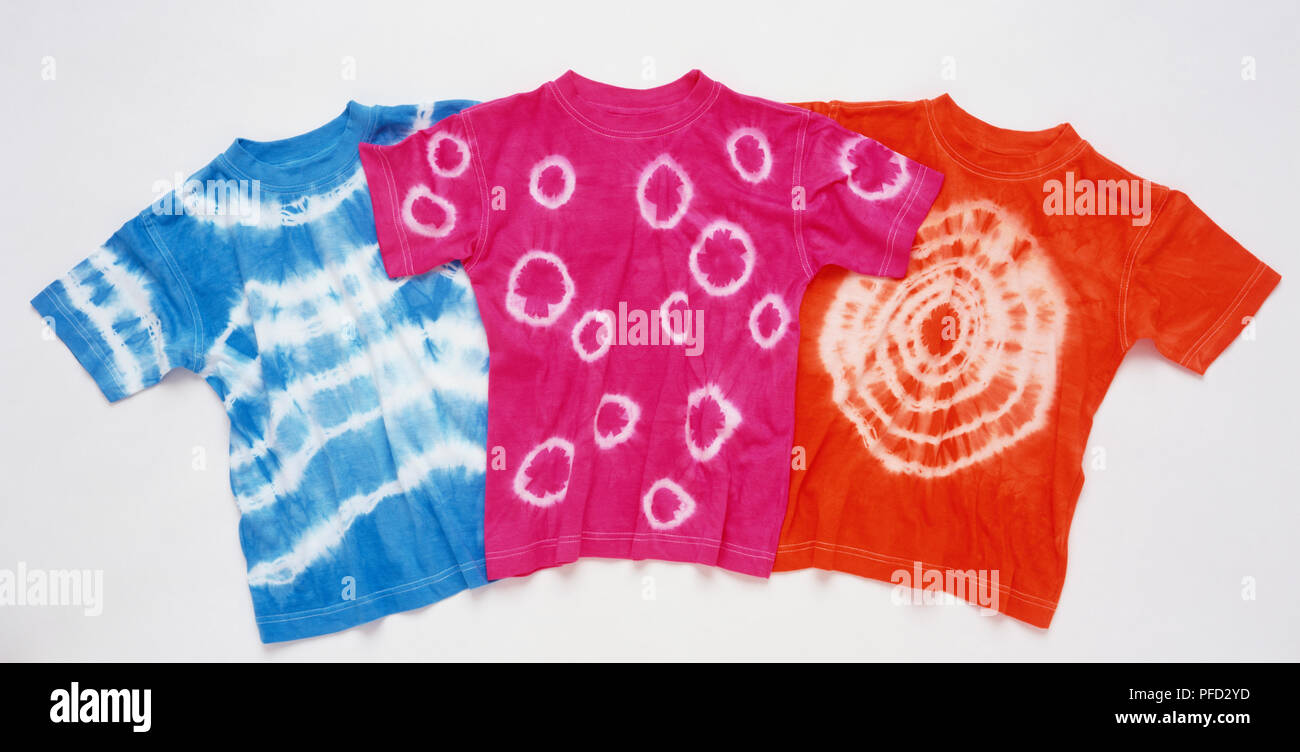 Three dyed t-shirts, red pink and blue respectively and each with different patterns. - Stock Image