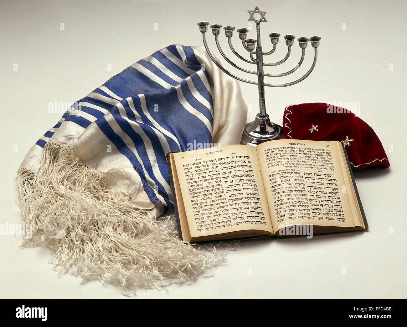 Menorah or branched candlestick, yarmulke or kipa, Jewish prayer book, and tallith or prayer shawl. - Stock Image