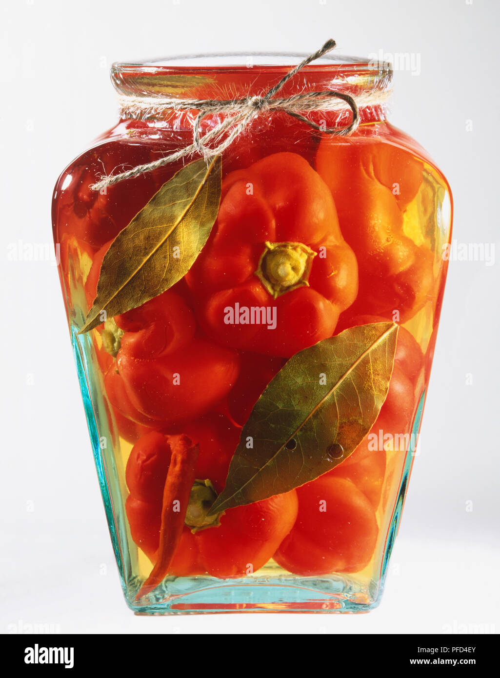 Glass jar with red peppers and herbs preserved in oil - Stock Image