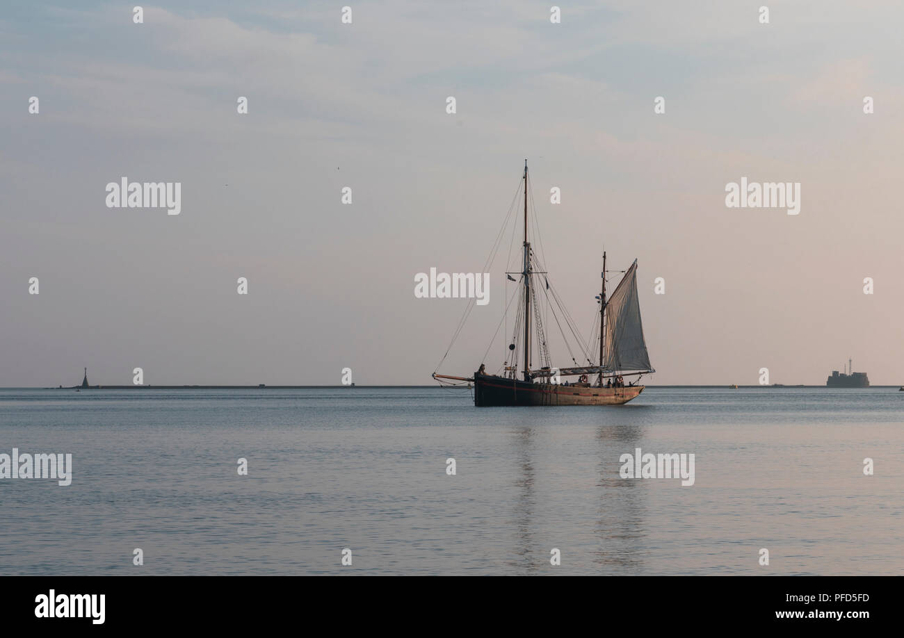Ketch quietly rests in its dusk time anchorage at Jennycliffe, Devon - Stock Image