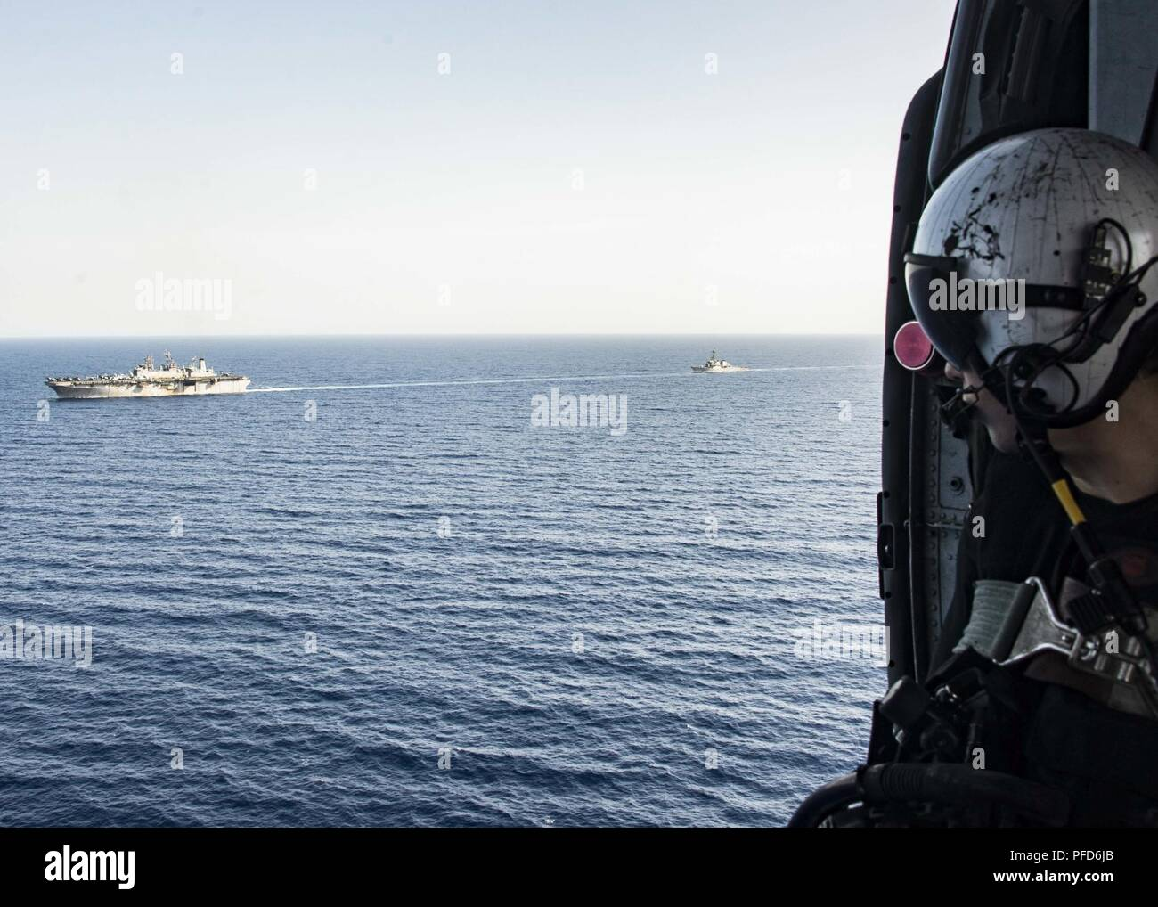 5TH FLEET AREA OF OPERATIONS (June 8, 2018) Naval Air Crewman (Helicopter) 2nd Class Luke Elliott, assigned to Helicopter Sea Combat Squadron (HSC) 28, observes a replenishment-at-sea between the Wasp-class amphibious assault ship USS Iwo Jima (LHD 7) and the fleet replenishment oiler USNS Big Horn (T-AO 198) from an MH-60S Sea Hawk, June 8, 2018. Iwo Jima, homeported in Mayport, Fla., is on deployment to the U.S. 5th Fleet area of operations in support of maritime security operations to reassure allies and partners, and preserve the freedom of navigation and the free flow of commerce in the r Stock Photo