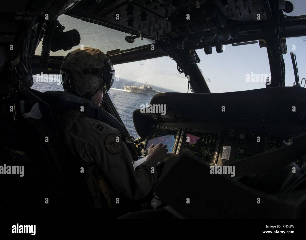 5TH FLEET AREA OF OPERATIONS (June 8, 2018) Lt. Bond Robinson, aircraft commander of an MH-60S Sea Hawk, attached to Helicopter Sea Combat Squadron (HSC) 28, conducts a replenishment-at-sea with the Wasp-class amphibious assault ship USS Iwo Jima (LHD 7, June 8, 2018. Iwo Jima, homeported in Mayport, Fla., is on deployment to the U.S. 5th Fleet area of operations in support of maritime security operations to reassure allies and partners, and preserve the freedom of navigation and the free flow of commerce in the region. Stock Photo