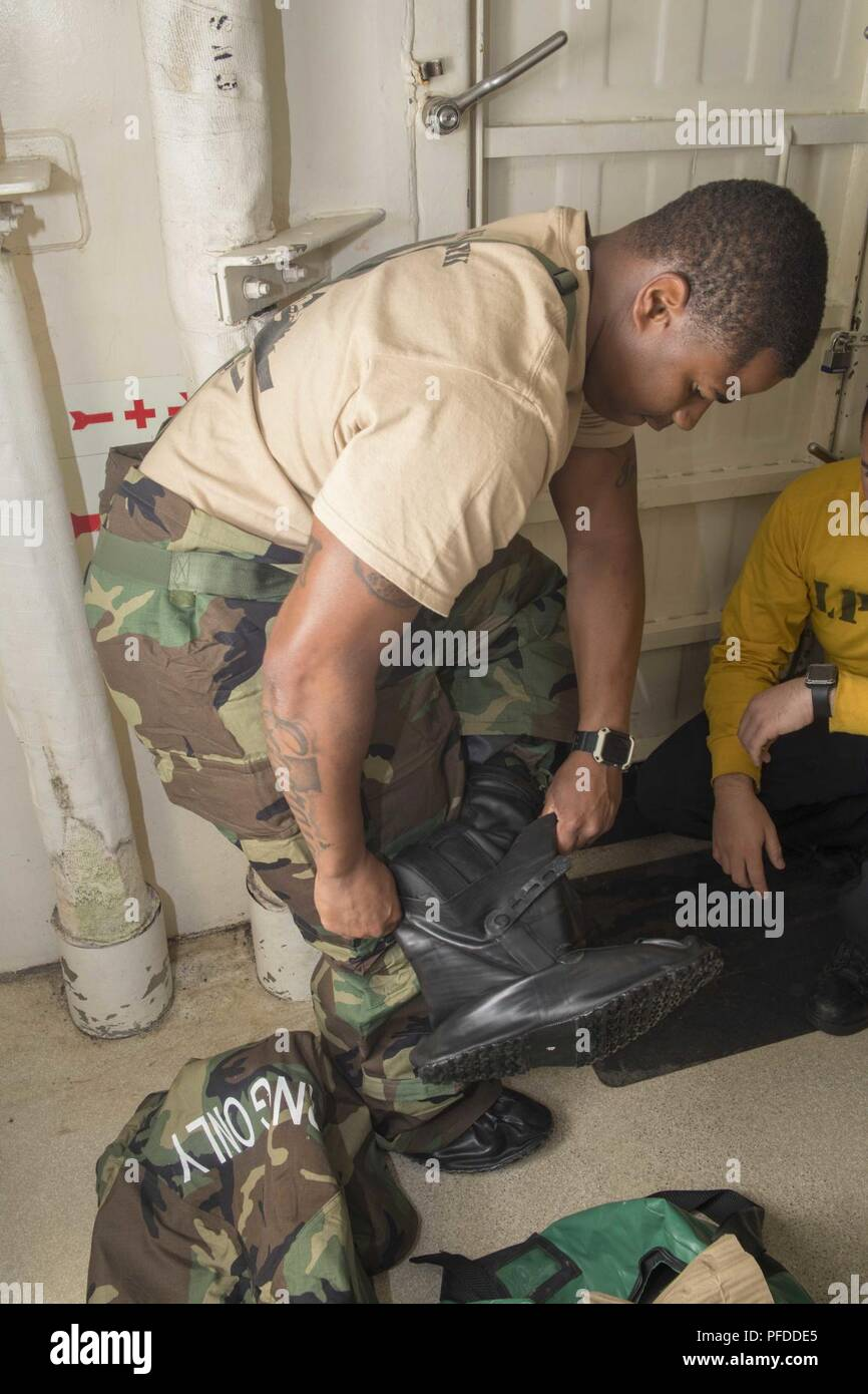 MEDITERRANEAN SEA (May 30, 2018) Aviation Support Equipment Technician 2nd Class Kentorius Hazelwood, from Camilla, Georgia, dons a chemical, biological and radiological (CBR) overgarment during a CBR training exercise aboard the San Antonio-class amphibious transport dock ship USS New York (LPD 21) May 30, 2018. New York, homeported in Mayport, Florida, is conducting naval operations in the U.S. 6th Fleet area of operations in support of U.S. national security interest in Europe and Africa. - Stock Image