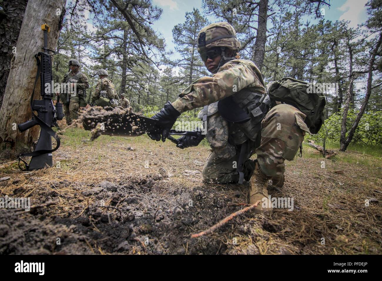 A U.S. Army National Guard Soldier from New Jersey's 250th Finance Detachment shovels out a hasty fighting position during training on Joint Base McGuire-Dix-Lakehurst, N.J., June 5, 2018. The 250th Finance Detachment was trained in base defense by instructors from the U.S. Army's 174th Infantry Brigade. - Stock Image