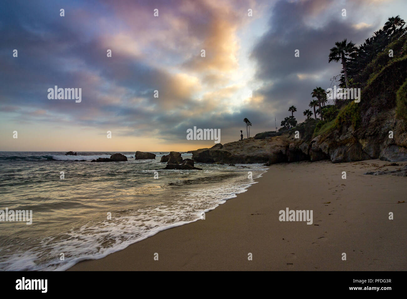Stunning coastal view of a cloudy sky with waves crashing onto the beach at sunset, Divers Cove, Laguna Beach, California Stock Photo